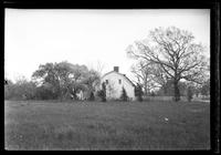 Unidentified Dutch Colonial house in good repair, on fenced property, undated. Side view.