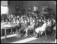 Children seated, listening (story time?) in the reading room of an unidentified branch of the Queens Borough Public Library, ca. 1910.