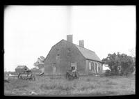 Unidentified Dutch Colonial farmhouse with horse-drawn tractor's / plows parked in foreground, undated.
