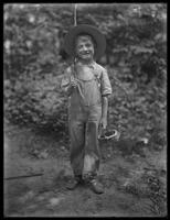 William Gray Hassler (little boy) in straw hat and overalls, carrying fishing pole (?) and basket in the woods, August 20, 1911. Full-length portrait shot.