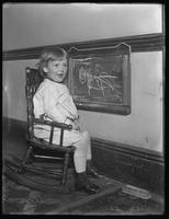 Seymour boy in play smock seated in rocking chair beside blackboard, undated.