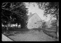 Side view of unidentified wood-shake house shaded by trees in front, with cottage (?) and fruit trees at rear, undated.