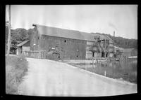 Huntington, Long Island: [unidentified old wood-shake barn or water mill, possibly used as a clam shack, with larger industrial building beyond, undated.]