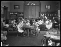 Children reading in the reading room of an unidentified branch of the Queens Borough Public Library, ca. 1910.
