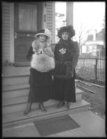 Elizabeth and Margaret Creighton posed on front porch steps in fur-trimmed coats, hats, and muffs, Irvington, N.Y., undated.