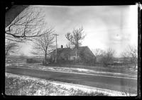 Two unidentified saltbox houses by the road, undated. Winter view with snow.