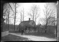 Unidentified Dutch Colonial house in woods, undated. Man walking in foreground (blurry).