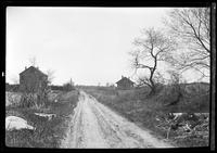 Dirt road leading to unidentified houses in distance, undated.