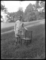 William Gray Hassler (little boy) in play clothes, standing by a chair in the park, July 28, 1912.