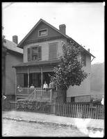 Four children pose on the porch of a house on a river or lake, ca. 1910.