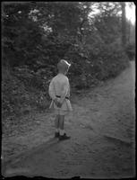 William Gray Hassler (little boy) standing in a narrow country lane with his back to the camera, ca. 1911.