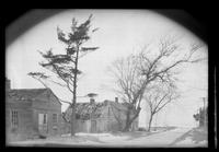 Several unidentified wood-shake buildings by a road, undated. Roof is collapsing on the center house.