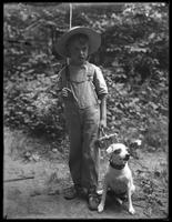 William Gray Hassler (little boy) in straw hat and overalls, carrying fishing pole (?) and basket, posed in the woods with a small dog (Bessie), August 20, 1911.