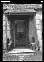 Front door of an unidentified Wood-shake house, undated. Door open to show interior flowered wallpaper and small decorative table.