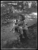 William Gray Hassler (little boy) in straw hat and overalls, posed seated in the woods with a small dog (Bessie), August 20, 1911.