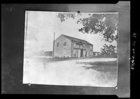 Photograph of a large unidentified barn at a bend in a road, undated.