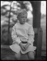 William Gray Hassler (little boy) sitting on a rustic fence, ca. 1911.