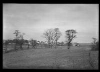 Empty fields, with unidentified houses visible in the distance, undated.