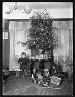 Seymour boy posed seated on tricycle beside Christmas tree in parlor, Christmas 1912.