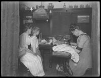 Ethel Gray Magaw Hassler, William Gray Hassler (little boy), Harriet E. Hassler and Reddy (cat) in the dining area of 150 Vermilyea Avenue, Apartment 44, New York City, undated. Harriet Hassler operating a sewing machine.