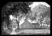 Side view of unidentified house shaded by very tall trees, undated.