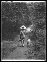 William Gray Hassler (little boy) in straw hat and overalls, carrying fishing pole (?) and basket, walking down a path in the woods with a small dog (Bessie), August 20, 1911. Back to camera.