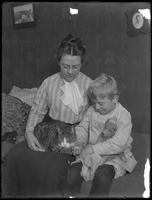 Harriet E. Hassler and William Gray Hassler (little boy), seated with tabby cat (Reddy) and teddy bear, ca. 1911.