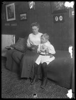 Ethel Gray Magaw Hassler and William Gray Hassler (little boy) seated on couch, reading, ca. 1912. William holds a stuffed elephant.