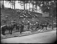 Northern border of New York City at Broadway at 263rd Street, Bronx, looking north, June 8, 1914. 'Good-bye New York City' sign, horse-drawn carts, and Italian laborers working in a stone retaining wall visible.