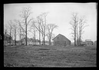 Side view of unidentified saltbox house surrounded by newer Dutch Colonial Revival houses, undated. Empty field in foreground.
