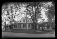 Unidentified Dutch Colonial house with scroll-topped columns supporting front porch, undated.