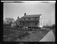 Newtown: [unidentified old wood house with advertisement painted on the side, undated.]