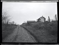Newtown: [dirt track through an unidentified field, undated. House in distance.]