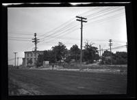 Newtown: [unidentified stretch of unpaved road with partially visible houses, man on sidewalk, undated.]