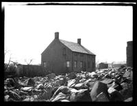 Newtown: [3/4 view of unidentified  wood-shake house with stones scattered in foreground, undated.]
