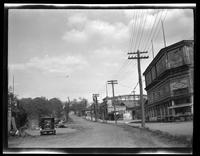 Newtown: [unidentified commercial buildings along unpaved road, undated. Gas tank frame in background.]
