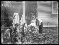 Anna E. Bjorkman and Odessa France Bjorkman watch while Herman Bjorkman works a vegetable garden, undated (ca. 1920).