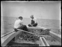 Two unidentified fishermen in a boat with harvested oysters, undated (ca. 1920).