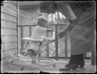Odessa France Bjorkman playing with daughter Virginia Bjorkman in a walker on a porch, undated (ca. 1920).