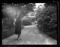 Odessa France Bjorkman standing at the end of a driveway, house in the background, undated (ca. 1925-1930).