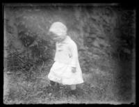 Toddler Virginia Bjorkman walking in grass by a rock face, undated (ca. 1920-1925).