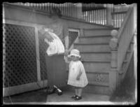Odessa France Bjorkman posing with an infant William Bjorkman and toddler Virginia Bjorkman at the base of some house stairs, undated (ca. 1920-1925).