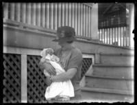 Odessa France Bjorkman posing with an infant William Bjorkman at the base of some house stairs, undated (ca. 1920-1925).