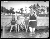 Odessa France Bjorkman with William Bjorkman, Virginia Bjorkman, and  an unidentified boy pose in bathing suits on a dock, undated (ca. 1925-1930).