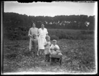 Odessa France Bjorkman, William Bjorkman, Virginia Bjorkman, and  an unidentified woman and child with a wheelbarrow full of melons or gourds, undated (ca. 1925-1930). Blurred.