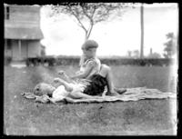Two unidentified children playing on the front lawn of a house, Savannah, Georgia or Jacksonville, Florida, undated, (ca. 1920).