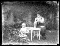 Odessa France Bjorkman and her son William Bjorkman seated at a table in a garden, undated (ca. 1925-1930).