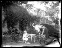 Odessa France Bjorkman with an infant William Bjorkman seated at a table in a garden, undated (ca. 1925-1930).