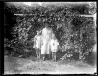 Anna E. Bjorkman poses with grandchildren Virginia Bjorkman and William Bjorkman under a grape arbor, undated (ca. 1920-1930).