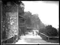 Unidentified child and adult walking along the path in front of Kearney House, Palisades Interstate Park, New Jersey, (ca. 1930-1935).